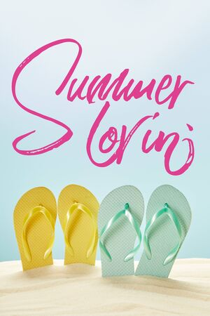 summer yellow and blue flip flops in golden sand isolated on blue with summer lovin lettering