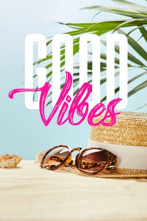 sunglasses near straw hat and seashells in summertime isolated on blue with good vibes lettering Banco de Imagens