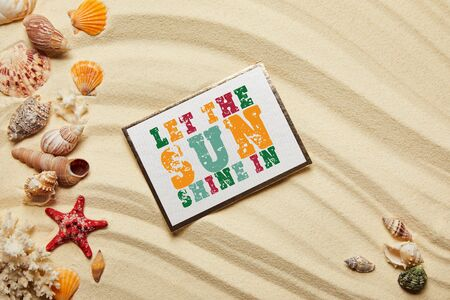 top view of card with let the sun shine in lettering near seashells, red starfish and corals on sandy beach