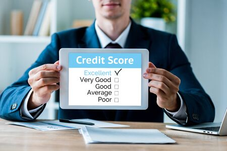 selective focus of happy man holding digital tablet with credit score letters in office Фото со стока