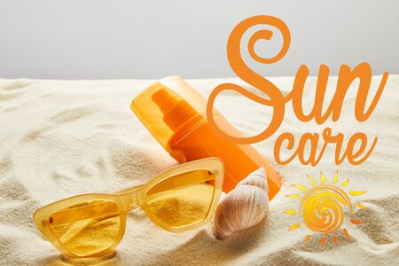 yellow stylish sunglasses and sunscreen in orange bottle on sand with seashell on grey background with sun care lettering 版權商用圖片
