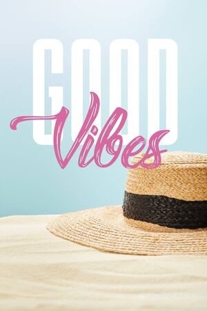 selective focus of straw hat on golden sand in summertime isolated on blue with good vibes illustration