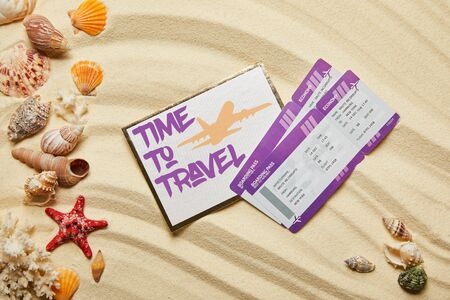 top view of card with time to travel letting near air tickets and seashells on sandy beach