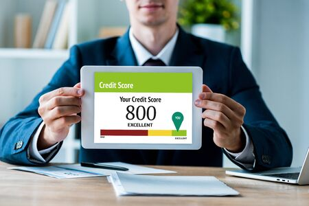 selective focus of happy man holding digital tablet with your credit score lettering in office