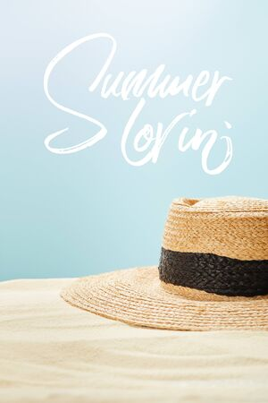 selective focus of straw hat on golden sand in summertime isolated on blue with summer lovin lettering Stock fotó