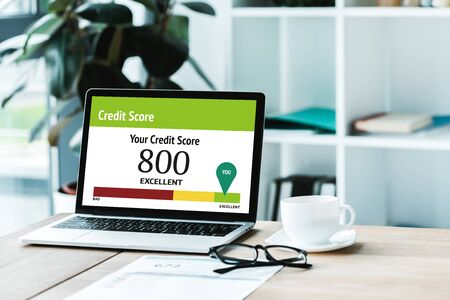 cup of coffee near laptop with credit score lettering and numbers on screen Banco de Imagens - 131381237