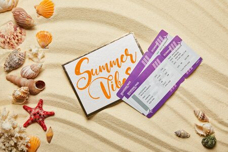 top view of card with summer vibes letting near air tickets and seashells on sandy beach Stockfoto
