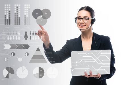 attractive call center operator holding laptop and pointing with finger at infographics on grey and white background