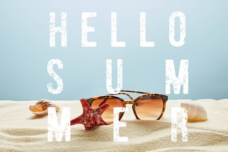 brown stylish sunglasses on sand with seashells and starfish on blue background with hello summer lettering