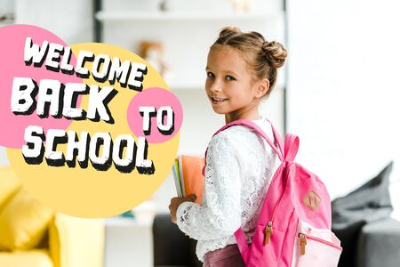 smiling schoolchild holding books while standing with backpack near welcome back to school letters