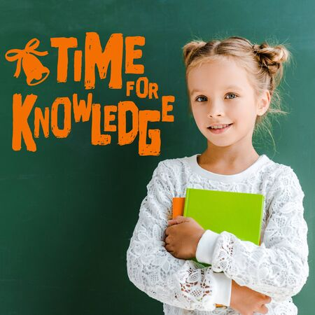 happy schoolgirl smiling while standing with books near time for knowledge lettering on green