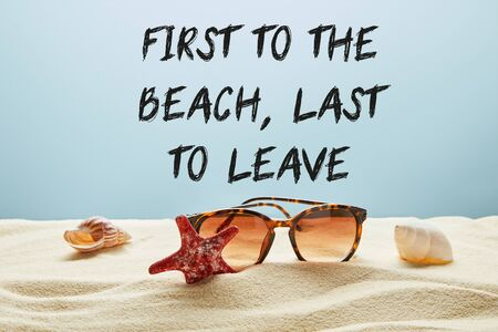brown stylish sunglasses on sand with seashells and starfish on blue background with first to the beach, last to leave lettering