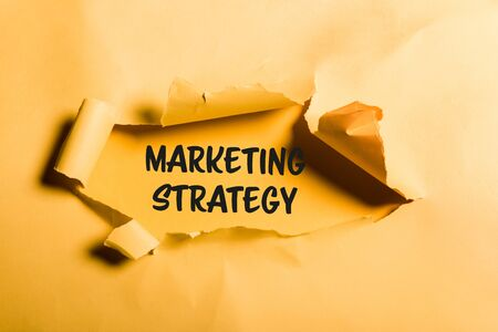 tattered paper with marketing strategy lettering and rolled edges on orange