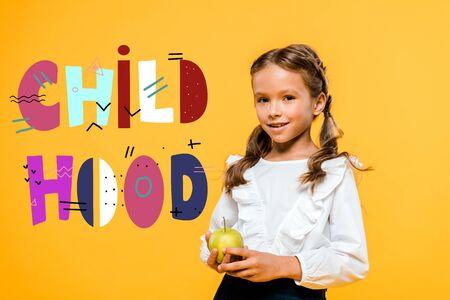 happy schoolchild holding tasty apple near childhood lettering on orange