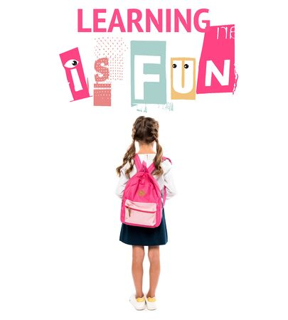 back view of schoolchild standing with pink backpack near learning is fun lettering on white Фото со стока