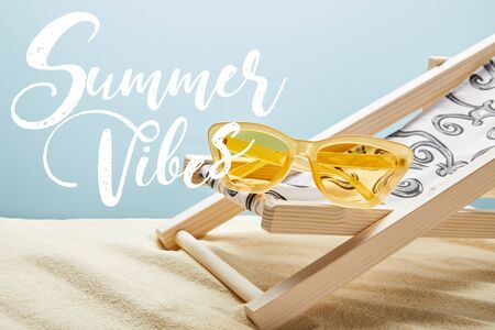yellow stylish sunglasses on deck chair on sand and blue background with summer vibes lettering