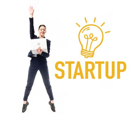 smiling businesswoman using laptop while jumping near startup word and drawn electric bulb isolated on white 版權商用圖片