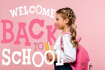 side view of happy kid holding books while standing with backpack near welcome back to school lettering on pink