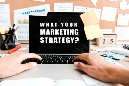 cropped view of woman using laptop with what your marketing strategy lettering on screen near sticky notes 版權商用圖片 - 131380442