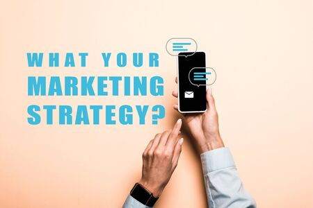 cropped view of woman pointing with finger at smartphone with what your marketing strategy lettering on pink 版權商用圖片