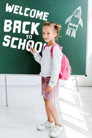 cute schoolgirl standing with backpack and holding chalk near welcome back to school lettering on green chalkboard Фото со стока