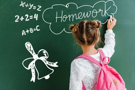 back view of kid near green chalkboard with homework letters on green 写真素材 - 131322673