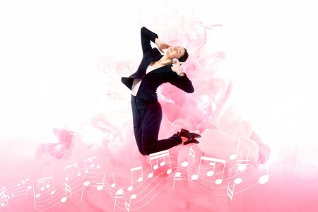 young businesswoman listening music in headphones while jumping on background with music notes and pink smoke splashes isolated on white