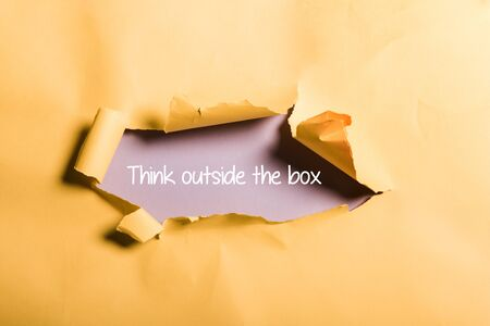 tattered paper with think outside box lettering and rolled edges on orange Stockfoto - 131322012