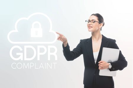 attractive businesswoman holding laptop and pointing with finger at gdpr compliant safety lock icon on grey background