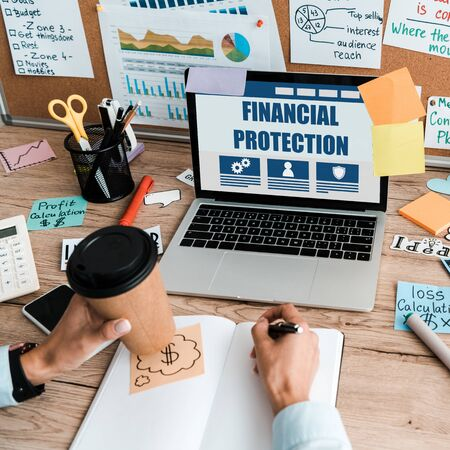 cropped view of businesswoman with pen and paper cup near laptop with financial protection on screen  Фото со стока