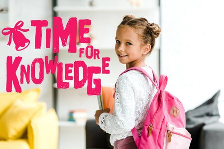 smiling schoolchild holding books while standing with backpack near time for knowledge letters
