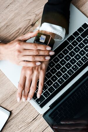 top view of woman touching smart watch with social media near laptop  Stock fotó
