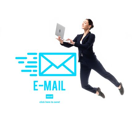 smiling businesswoman levitating while using laptop near e-mail icon and click here to send lettering isolated on white