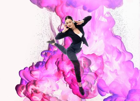 young businesswoman dancing in headphones on background with pink and purple smoke splashes isolated on white