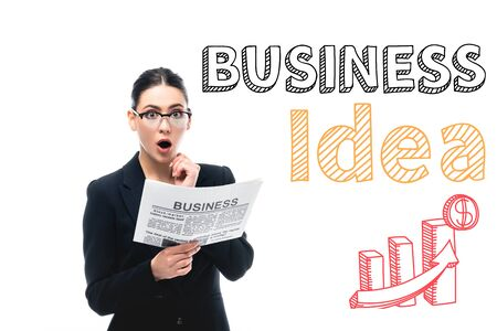 shocked businesswoman looking at camera while holding newspaper near business idea lettering, graphs and dollar sign isolated on white
