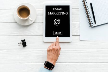 top view of woman pointing with finger at digital tablet with email marketing lettering on screen near cup of coffee and paper clip