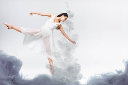 young graceful ballerina in white dress dancing in grey smoke on grey background