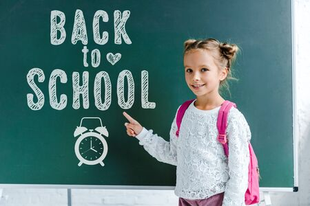 cheerful kid smiling while pointing with finger at back to school lettering on green chalkboard Фото со стока