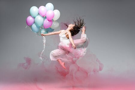 beautiful ballerina dancing with festive balloons near pink smoke splashes on grey background Stok Fotoğraf
