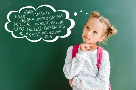pensive kid standing with backpack near chalkboard with greetings lettering on green Фото со стока