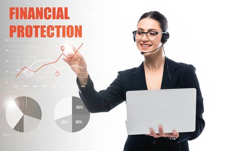 smiling call center operator holding laptop and pointing with finger at financial protection lettering and infographics on grey and white background