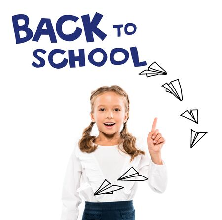 happy kid pointing with finger at back to school lettering on white