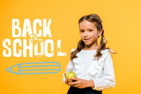 happy schoolchild holding tasty apple near back to school lettering on orange