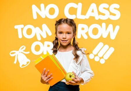 happy schoolchild holding tasty apple and books near no class tomorrow lettering on orange Stock Photo