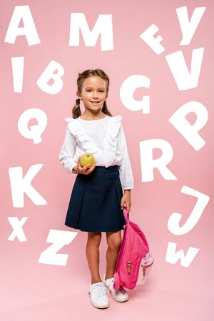happy kid holding tasty and green apple and backpack near letters on pink