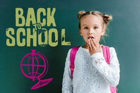surprised schoolgirl covering mouth near chalkboard with back to school letters on green