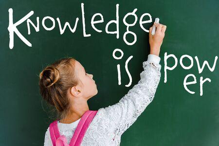 schoolchild holding chalk near chalkboard with knowledge is power lettering on green Фото со стока