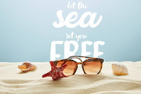 brown stylish sunglasses on sand with seashells and starfish on blue background with let the sea set you free lettering 版權商用圖片