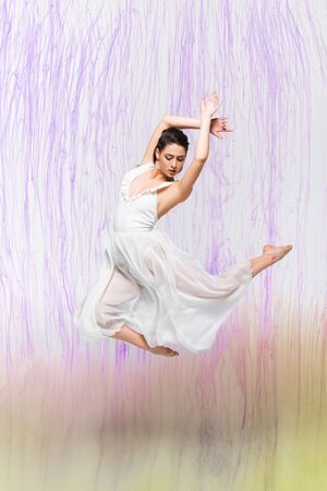 attractive ballerina in white dress dressing on grey background with colorful spills Stok Fotoğraf