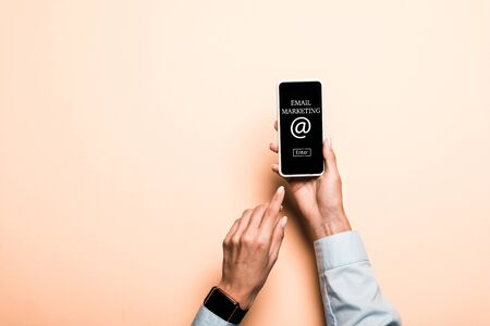cropped view of woman pointing with finger at smartphone with email marketing lettering on pink Stock fotó